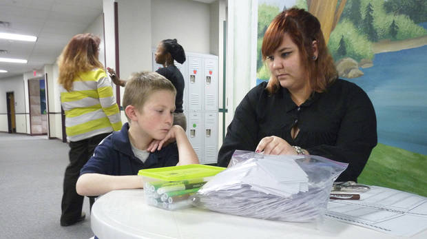 Mark Twain Elementary second-grader Corey Henson, 8, receives extra help with his vocabulary from teacher's assistant Amber Ferguson. Oklahoma Watch photo.  <strong></strong>