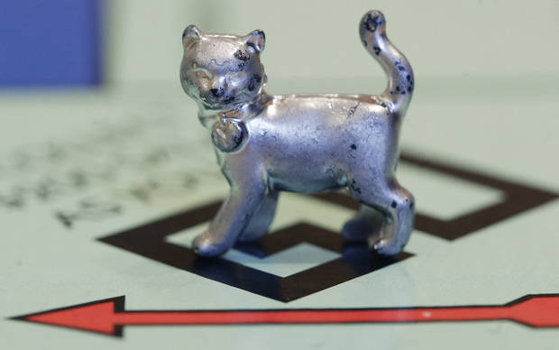 The newest Monopoly token, a cat, rests on the game board at Hasbro Inc. headquarters, in Pawtucket, R.I., Tuesday, Feb. 5, 2013. Voting on Facebook determined that the cat would replace the iron token. (AP Photo/Steven Senne) ORG XMIT: RISR104