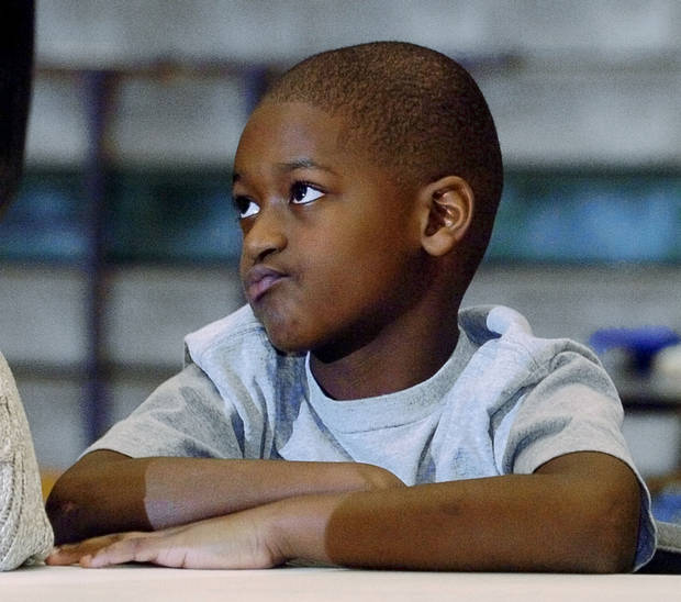 Trevan Smith, 9, listens as older brother Reggie Smith prepares to announce he will attend the University of Oklahoma on Feb. 2, 2005.  Photo by Steve Sisney, The Oklahoman Archive