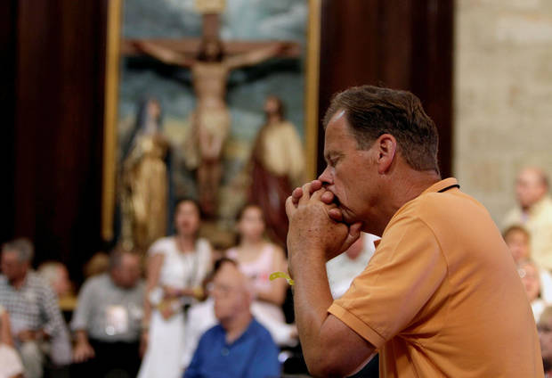 A pilgrim prays during a mass conducted by Miami's Archbishop Thomas Wenski celebrates a mass with pilgrims from Florida at the Cathedral of Havana Tuesday March 27, 2012.  Wenski  led a pilgrimage of about 300 mostly Cuban-Americans to the island for Pope Benedict's XVI visit.(AP Photo/Franklin Reyes) ORG XMIT: HAV115