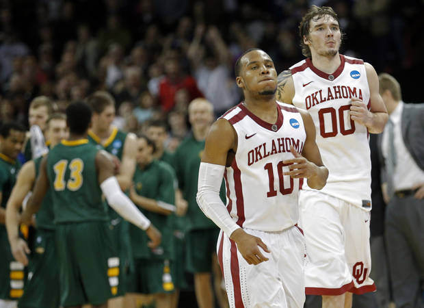 Oklahoma's Jordan Woodard (10) and Ryan Spangler (00) walk off the court in the final seconds of overtime during the NCAA men's basketball tournament game between the University of Oklahoma and North Dakota State at the Spokane Arena in Spokane, Wash., Thursday, March 20, 2014. Oklahoma home lost 80-75. Photo by Sarah Phipps, The Oklahoman
