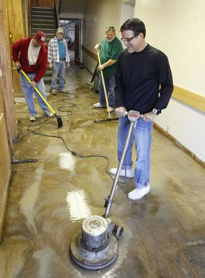 Jim Williams, front, prepares a concrete floor for finishing Saturday as members of Southern Nazarene University's class of 1980 work to help Love Link Ministries Inc. prepare to move into a new building in downtown Oklahoma City. In the background are Allan Cypert, left,  Jerry Taylor, center, and Barry Burkhart. PHOTO BY PAUL HELLSTERN, THE OKLAHOMAN <strong>PAUL HELLSTERN</strong>