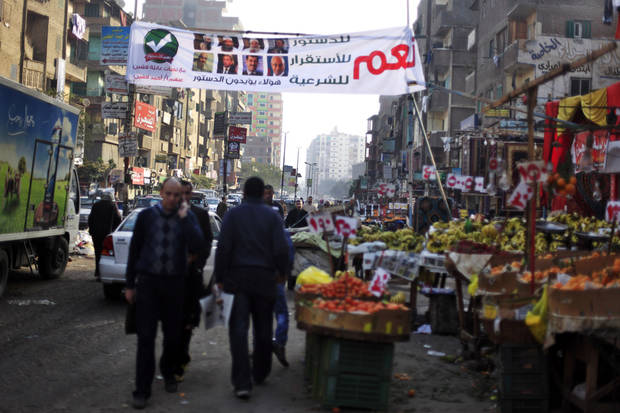 "Egyptians walk under a banner with Arabic that reads, "" Yes to the constitution, stability, and legality,"" during a referendum on a disputed constitution drafted by Islamist supporters of President Mohammed Morsi, in Cairo, Egypt, Saturday, Dec. 15, 2012. Egyptians were voting on Saturday on a proposed constitution that has polarized their nation, with Morsi and his Islamist supporters backing the charter, while liberals, moderate Muslims and Christians oppose it. (AP Photo/Khalil Hamra)"