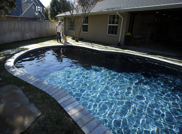 Eilizabeth Greenhey pets Dawson beside the swimming pool of her home on Tuesday, Nov. 6, 2012 in Norman, Okla.  Photo by Steve Sisney, The Oklahoman