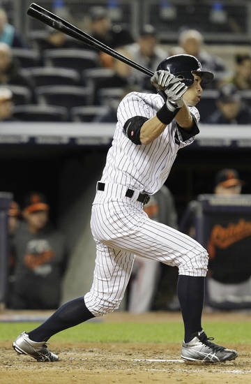 New York Yankees' Ichiro Suzuki, of Japan, hits an RBI double during the sixth inning of Game 5 of the American League division baseball series against the Baltimore Orioles, Friday, Oct. 12, 2012, in New York. The Yankees' Derek Jeter scored on the hit. (AP Photo/Kathy Willens)