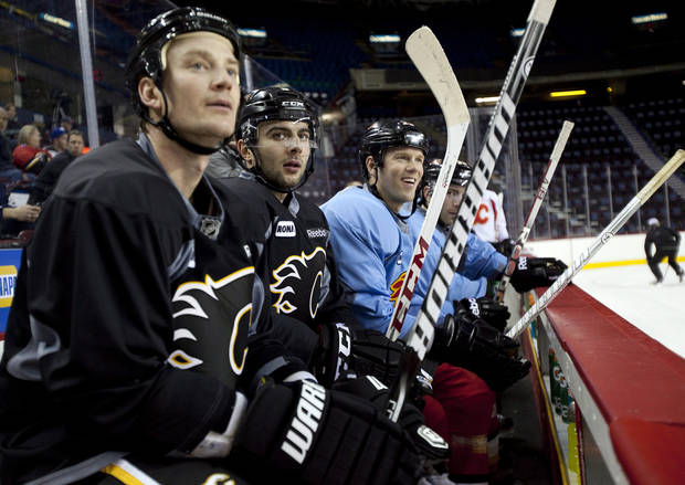 Calgary Flames, left to right, Jay Bouwmeester, Mark Giordano, and Brad Winchester, watch a drill during NHL hockey training camp in Calgary,  Alberta, Monday, Jan. 14, 2013. (AP Photo/The Canadian Press, Jeff McIntosh)