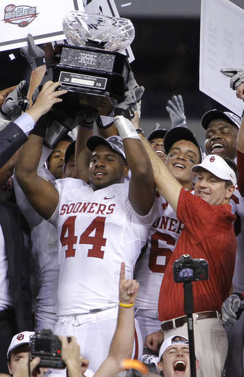 Oklahoma's Jeremy Beal and coach Bob Stoops hold up the Big 12 Championship trophy after the 23-20 win over Nebraska during the Big 12 football championship game between the University of Oklahoma Sooners (OU) and the University of Nebraska Cornhuskers (NU) at Cowboys Stadium on Saturday, Dec. 4, 2010, in Arlington, Texas.  Photo by Chris Landsberger, The Oklahoman