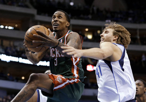 Milwaukee Bucks' Brandon Jennings (3) gets past Dallas Mavericks' Dirk Nowitzki (41) during the first half of an NBA basketball game Tuesday, Feb. 26, 2013, in Dallas. (AP Photo/Tony Gutierrez)