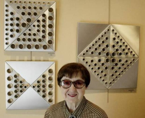 "Artist Alexandra Alaupovic and some of her sculptures. Alaupovic is a Yugoslavian-born artist who moved to the U.S. in the 1950's and has lived and worked in Oklahoma for 40 years. ART, ARTWORK, WALL HANGING: Posed in front of three wall hangings titled ""Triangular Variation"", 1975, Aluminum. Staff photo by Doug Hoke."