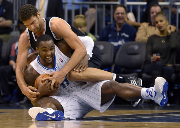 Orlando Magic forward Glen Davis (11) is fouled by Brooklyn Nets center Brook Lopez after gaining control of a loose ball during the first half of an NBA basketball game in Orlando, Fla., Friday, Nov. 9, 2012.(AP Photo/Phelan M. Ebenhack)