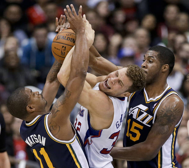 Los Angeles Clippers forward Blake Griffin, middle, struggles against Utah Jazz guard Earl Watson, left, and forward Derrick Favors for a rebound during the first half of an NBA basketball game in Los Angeles, Saturday, Feb. 23, 2013. (AP Photo/Chris Carlson)