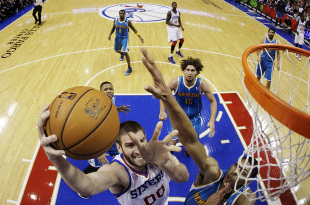 Philadelphia 76ers' Spencer Hawes (00) shoots as New Orleans Hornets' Anthony Davis, bottom right, defends and Robin Lopez (15) watches) during the first half of an NBA basketball game, Tuesday, Jan. 15, 2013, in Philadelphia. (AP Photo/Matt Slocum)