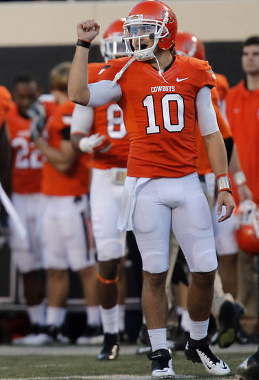 Oklahoma State's Clint Chelf (10) reacts after an extra point is made during the college football game between the Oklahoma State University Cowboys (OSU) and Texas Tech University Red Raiders (TTU) at Boone Pickens Stadium on Saturday, Nov. 17, 2012, in Stillwater, Okla.   Photo by Chris Landsberger, The Oklahoman