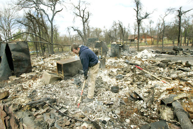 Sean Feroli searches for antique coins in the ashes of his father in-laws home at 347 Ash road that was destroyed in a wildfire in Choctaw, Oklahoma April 10, 2009.  Photo by Steve Gooch, The Oklahoman