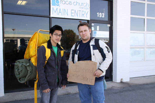"Philip Nguyen, left, and Dusty Buff, pastor of Grace Church in Norman, stand outside their church before leaving for a 10-day sojourn among the homeless. Buff's sign reads, ""I Need One Sent."" PHOTO PROVIDED BY DUSTY BUFF <strong></strong>"
