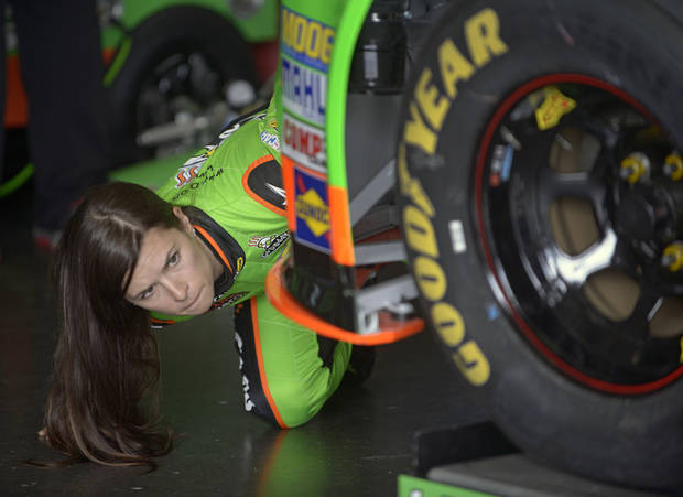 Danica Patrick checks out her car while crew members make adjustments in her garage during a practice session for the NASCAR Daytona 500 Sprint Cup Series auto race at Daytona International Speedway, Saturday, Feb. 16, 2013, in Daytona Beach, Fla. (AP Photo/Phelan M. Ebenhack) ORG XMIT: DBR115