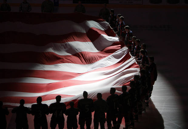 Hockey players and members of the military hold a giant American flag for military appreciation night at an AHL hockey game between the Oklahoma City Barons and the Grand Rapids Griffins at the Cox Convention Center in Oklahoma City, Saturday, March 24, 2012. Photo by Nate Billings, The Oklahoman