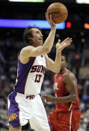 Phoenix Suns guard  Steve  Nash (13) spins and shoots a field goal as Atlanta Hawks guard Joe Johnson, rear, looks on in the fourth quarter of an NBA basketball game Friday, Feb. 19, 2010, in Phoenix. The Suns won 88-80. (AP Photo/Paul Connors)