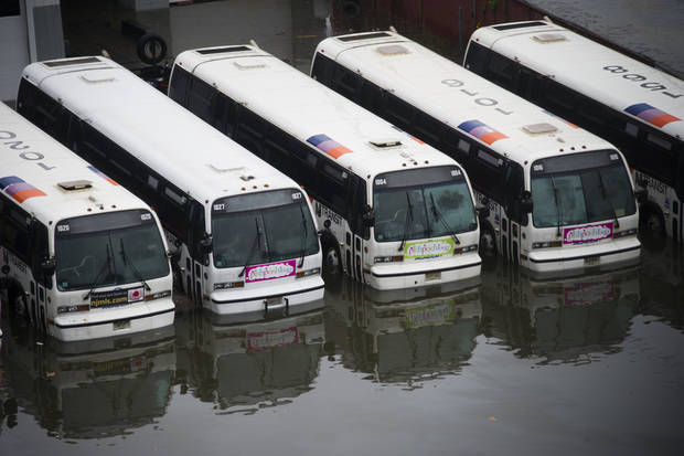 CORRECTS YELLOW CABS TO BUSES - A parking lot full of buses is flooded as a result of superstorm Sandy on Tuesday, Oct. 30, 2012 in Hoboken, NJ. (AP Photo/Charles Sykes) ORG XMIT: NYCS202