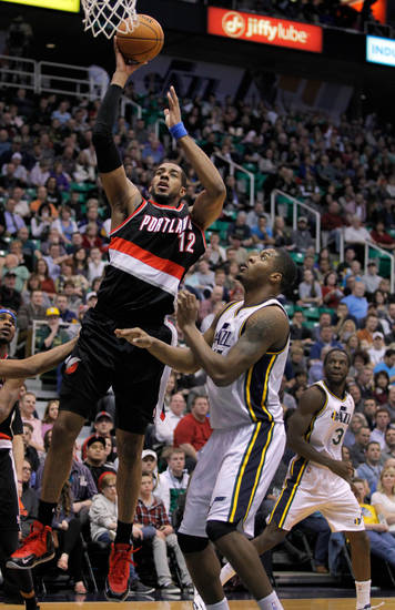 Portland Trail Blazers forward LaMarcus Aldridge (12) goes to the basket against Utah Jazz forward Derrick Favors, right, in the first half during an NBA basketball game on Friday, Feb. 1, 2013, in Salt Lake City. (AP Photo/Steve C. Wilson)