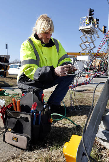 Right: Billy Unruh, with Traffic Systems Inc., installs new cable as other workers put in new controllers, lights and a left turn with flashing yellow sign.  PHOTOs BY STEVE SISNEY, THE OKLAHOMAN