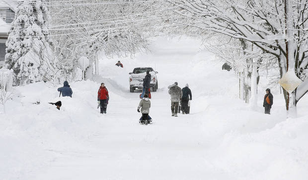 Residents start to dig out of the snow along a street in Providence, R.I., on Saturday, Feb. 9, 2013. A behemoth storm packing hurricane-force wind gusts and blizzard conditions swept through the Northeast overnight. (AP Photo/Stew Milne)