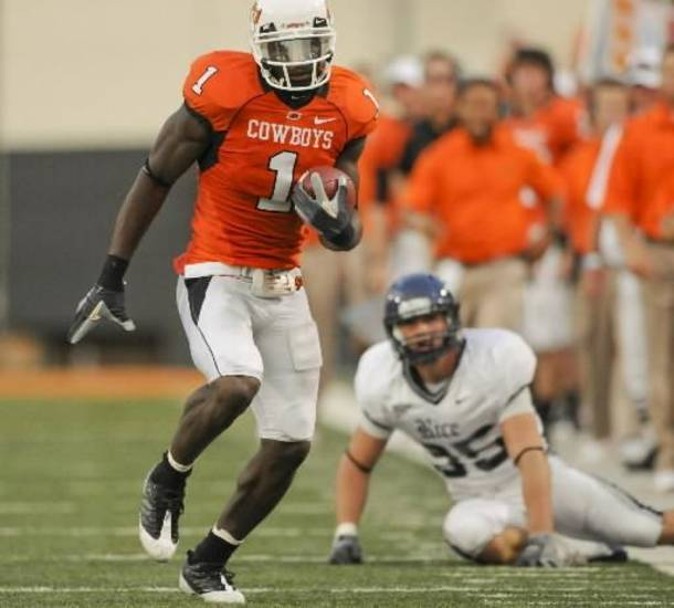 Rice safety Travis Bradshaw, right, watches as Oklahoma State wide receiver  Dez  Bryant, left, runs downfield during the first half of an NCAA college football game in Stillwater, Okla., Saturday, Sept. 19, 2009. Oklahoma State defeated Rice 41-24. (AP Photo/Brody Schmidt)