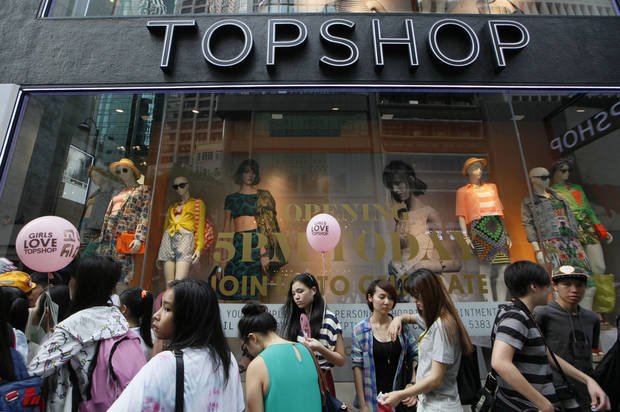 People line up to enter the first Topshop store in Hong Kong Thursday, June 6, 2013. British fashion chain Topshop opened its first Hong Kong outlet on Thursday, becoming the latest Western brand to brave the city's high rents in a bid to crack the lucrative China market.  (AP Photo/Kin Cheung)