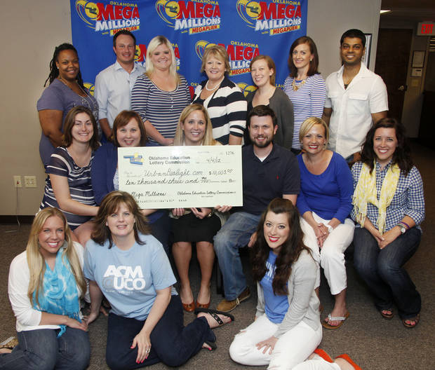 Employees from Urban Dealight gather for a photo with a big check Wednesday at the Oklahoma Lottery Commission after their office pool won $10,003 in the Mega Millions drawing last week.  Photo by Doug Hoke, The Oklahoman
