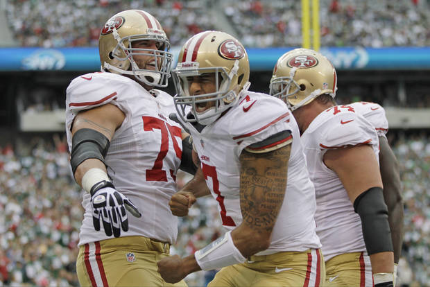 San Francisco 49ers quarterback Colin Kaepernick (7) celebrates after scoring a touchdown with teammates Alex Boone (75) and Joe Staley (74) during the first half of an NFL football game against the New York Jets Sunday, Sept. 30, 2012, in East Rutherford, N.J. (AP Photo/Kathy Willens)