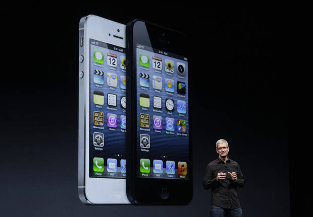 Apple CEO Tim Cook speaks in front of an image of the iPhone 5 during an Apple event in San Francisco, Wednesday, Sept. 12, 2012. (AP Photo/Jeff Chiu)