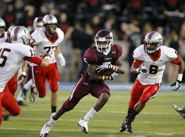 HIGH SCHOOL FOOTBALL: Jenks' Trey'Vonne Barr'e (center) runs under pressure from Union's Marquice Fletcher during the Backyard Bowl football game at the University of Tulsa on Friday, August 31, 2012. MATT BARNARD/Tulsa World ORG XMIT: DTI1208312124382260