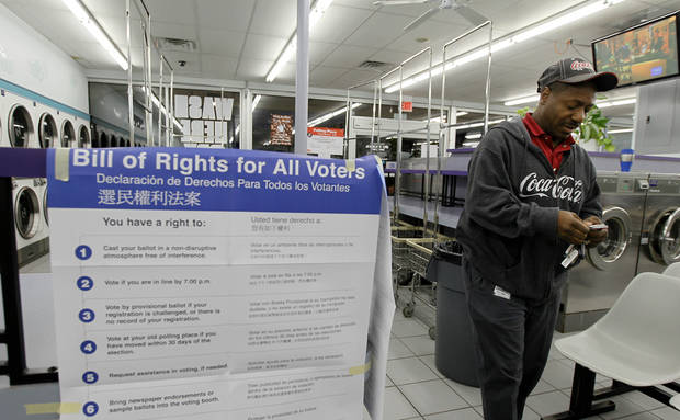 Darryl Williams waits to vote inside at the 24-hour Su Nueva Laundromat in Chicago's 13th Ward on Election Day, Tuesday, Nov. 6, 2012, in Chicago. (AP Photo/Charles Rex Arbogast)