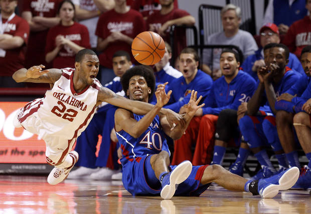 Oklahoma forward Amath M'Baye (22) reaches for the ball as Kansas forward Kevin Young passes it during the first half of an NCAA college basketball game in Norman, Okla., Saturday, Feb. 9, 2013. (AP Photo/Sue Ogrocki) ORG XMIT: OKSO101
