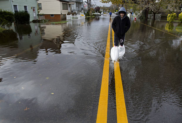 Deema Aitken, 21, of Little Ferry, N.J., walks on a street in Little Ferry, N.J. Tuesday, Oct. 30, 2012, as he keeps his lower legs dry with plastic bags on a flooded street left in the wake of superstorm Sandy.Sandy, the storm that made landfall Monday, caused multiple fatalities, halted mass transit and cut power to more than 6 million homes and businesses. (AP Photo/Craig Ruttle) ORG XMIT: NJCR120