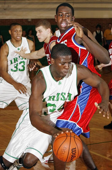 Michael Sosanya (34) of Bishop McGuinness drives past Wilson Holloway (14) of Oklahoma Christian as Blake Griffin (15) of OCS defends Daniel Orton (33) of Bishop McGuinness during the high school basketball game between Bishop McGuinness Fighting Irish and Oklahoma Christian School Saints at Bishop McGuinness in Oklahoma City, Friday, Dec. 15, 2006. By Nate Billings, The Oklahoman