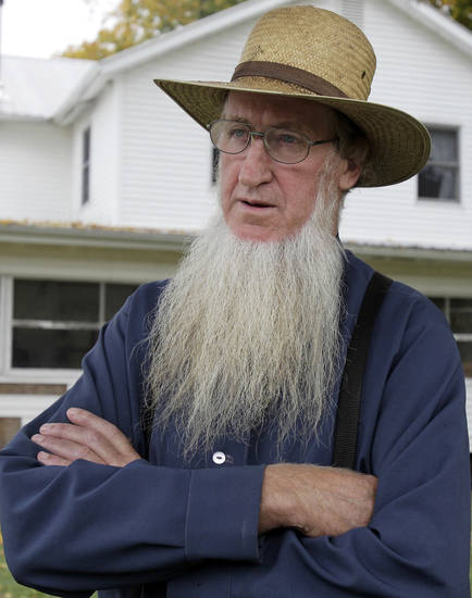 FILE - In this Oct. 10, 2011 file photo, Sam Mullet Sr. stands in the front yard of his home in Bergholz, Ohio. Mullet, 67, the ringleader in a series of unusual hair- and beard-cutting attacks on fellow Amish religious followers in the U.S. was sentenced Friday to 15 years in prison, and 15 family members received sentences of one year to seven years. The defendants were charged with a hate crime because prosecutors believe religious differences brought about the attacks. (AP Photo/Amy Sancetta, File)