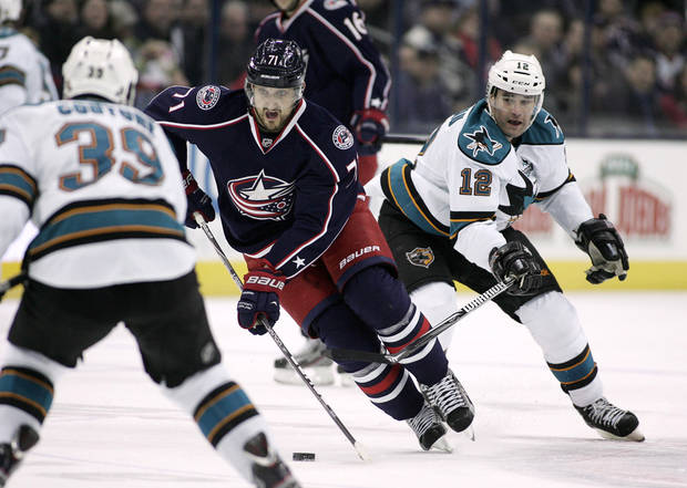Columbus Blue Jackets' Nick Foligno (71) races through San Jose Sharks defenders Logan Couture (39) and Patrick Marleau (12) during the second period of an NHL hockey game, Monday, Feb. 11, 2013, in Columbus, Ohio. (AP Photo/Mike Munden)