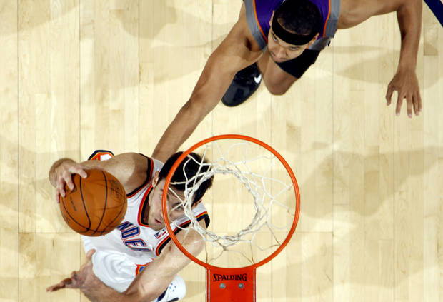 Oklahoma City's Nick Collison (4) shoots a basket as Phoenix's Jared Dudley during the NBA basketball game between the Oklahoma City Thunder and the Phoenix Suns, Sunday, Dec. 19, 2010, at the Oklahoma City Arena. Photo by Sarah Phipps, The Oklahoman