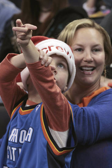 Crew VanPelt, 5, and his mother Carrie, watch the monitor during the first half as the Oklahoma City Thunder play the Orlando Magic in NBA basketball at the Chesapeake Energy Arena on Sunday, Dec. 25, 2011, in Oklahoma City, Okla.  Photo by Steve Sisney, The Oklahoman