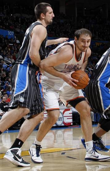 Oklahoma City's Nenad Krstic (12) tries to get past Ryan Anderson (33) of Orlando during the NBA basketball game between the Orlando Magic and Oklahoma City Thunder in Oklahoma City, Thursday, January 13, 2011. Photo by Nate Billings, The Oklahoman