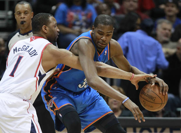 Oklahoma City Thunder forward Kevin Durant (35) drives against Atlanta Hawks forward Tracy McGrady (1) in the the first half of an NBA basketball game Saturday, March 3, 2012, in Atlanta. (AP Photo/John Bazemore)  ORG XMIT: GAJB116