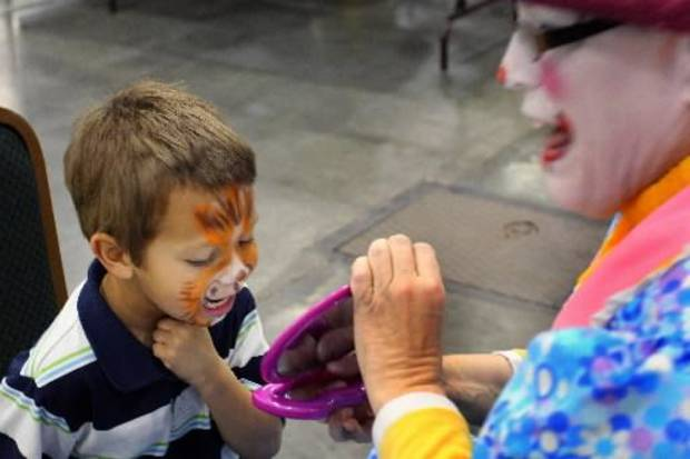 Ruben Ayala, Jr. reacts when he sees his new face in a mirror held by Flutterbye (Sabrina Evans) at the face painting booth during Opening Night 2012 festivities at the Cox Convention Center in downtown Oklahoma City, Saturday, December 31 2011. PHOTO BY HUGH SCOTT, FOR THE OKLAHOMAN