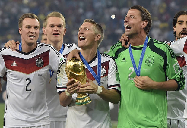 Germany's Bastian Schweinsteiger celebrates with the World Cup trophy after a 1-0 victory over Argentina on Sunday. (AP Photo)