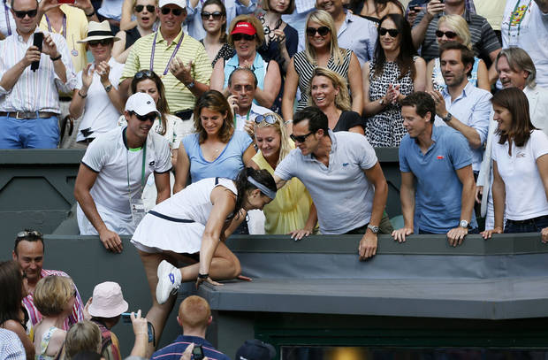 Marion Bartoli of France celebrates by climbing into the crowd after winning the Women's singles final match against Sabine Lisicki of Germany at the All England Lawn Tennis Championships in Wimbledon, London, Saturday, July 6, 2013.  (AP Photo/Stefan Wermuth, Pool)