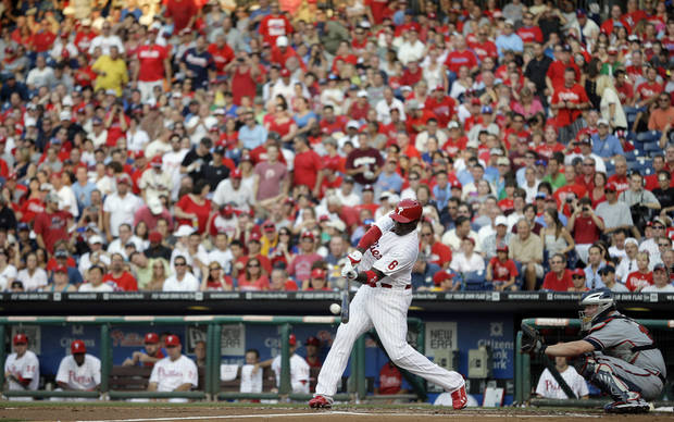 Philadelphia Phillies' Ryan Howard hits a double off Atlanta Braves starting pitcher Tim Hudson in the second inning of a baseball game, Friday, July 6, 2012, in Philadelphia. At right is Braves catcher Brian McCann. (AP Photo/Matt Slocum)