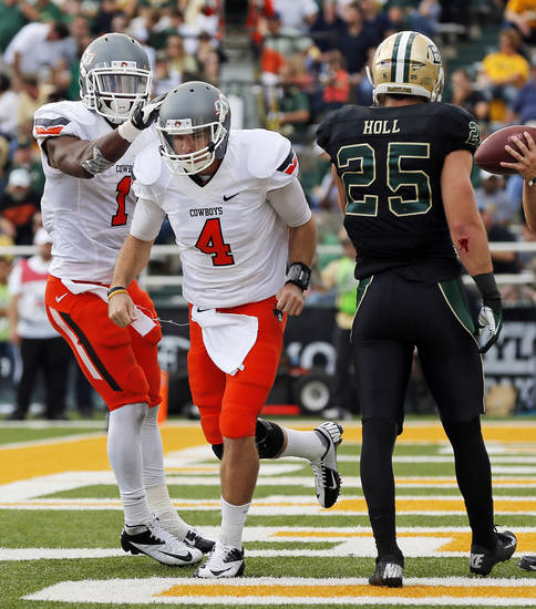 Oklahoma State's Joseph Randle (1) pats J.W. Walsh (4) on the helmet near Baylor's Sam Holl (25) after Walsh ran for a touchdown in the second quarter during a college football game between the Oklahoma State University Cowboys (OSU) and the Baylor University Bears at Floyd Casey Stadium in Waco, Texas, Saturday, Dec. 1, 2012. Photo by Nate Billings, The Oklahoman