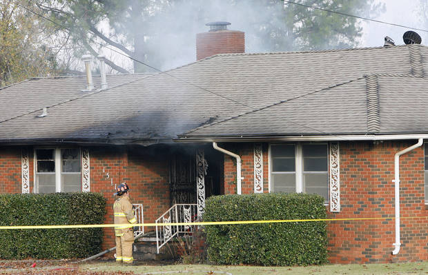 An Oklahoma City firefighter stands outside a house fire at 1511 SW 56 in Oklahoma City on Monday morning. By Paul B. Southerland