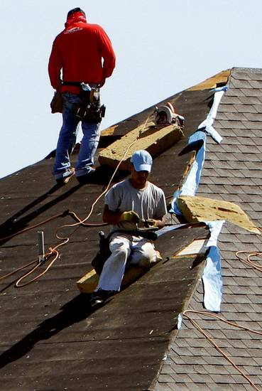 Workers roof a home in Norman. Competition for roofers and other construction subcontractors has grown fierce since the May tornadoes, builders say. <strong>STEVE SISNEY - THE OKLAHOMAN</strong>