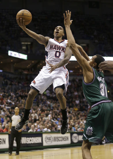 Atlanta Hawks' Jeff Teague (0) drives against Milwaukee Bucks' John Henson, right, during the first half of an NBA basketball game, Saturday, Feb. 23, 2013, in Milwaukee. (AP Photo/Jeffrey Phelps)
